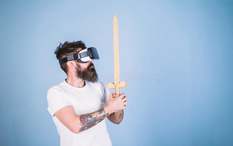 Hippie auf ernstem Gesicht genießen Spielspiel in der virtuellen Realität Gamerkonzept Mann mit Bart in VR-Gläsern, hellblau stockbild