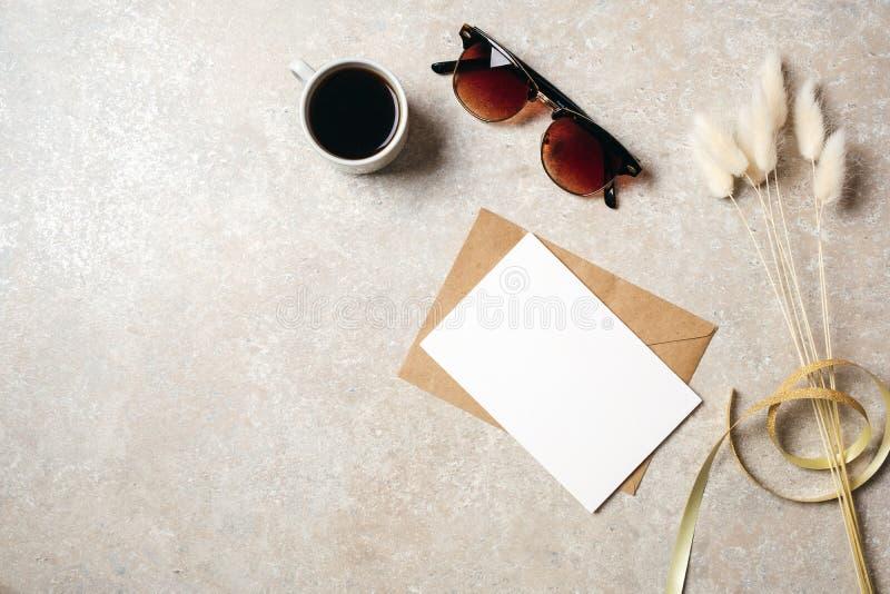 Hippie-Ausgangsschreibtischarbeitsplatz mit Sonnenbrille, Karte des leeren Papiers und Kraftpapier-Umschlag, trockene Blume mit B stockfotografie