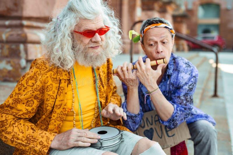 Hippie aux cheveux longs utilisant la chemise jaune lumineuse jouant les tambours images libres de droits
