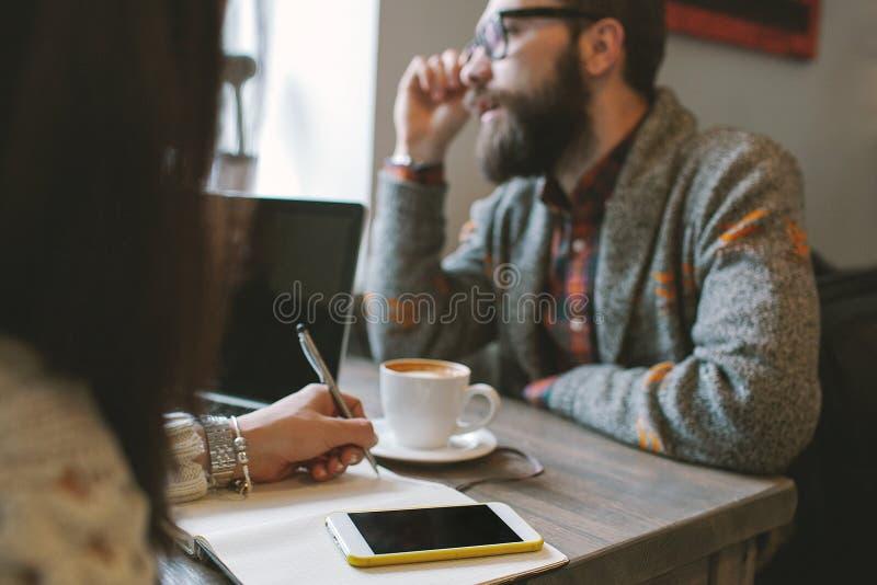 Hippie avec la barbe avec le smartphone et l'ordinateur portable sur la table donnant dedans image stock