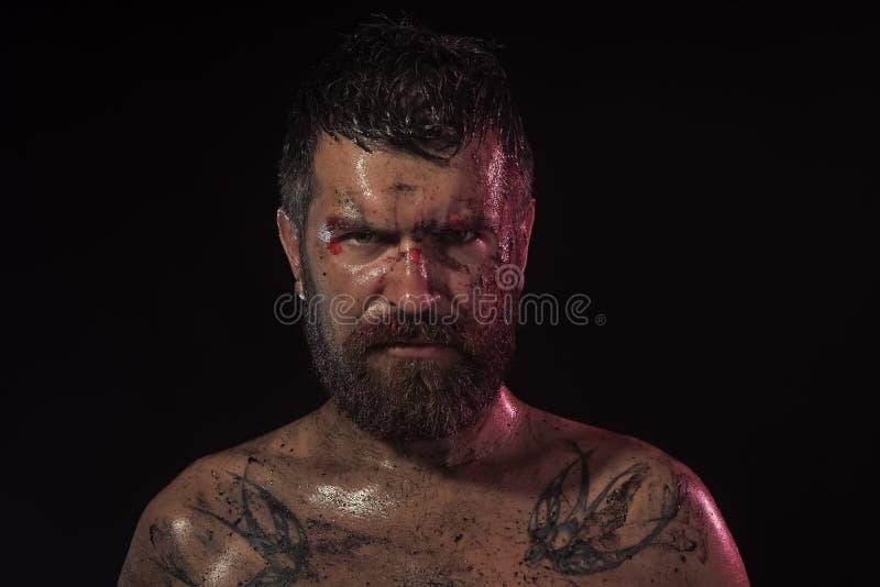 Hippie barbu avec le tatouage sur le coffre sur le fond noir photo stock