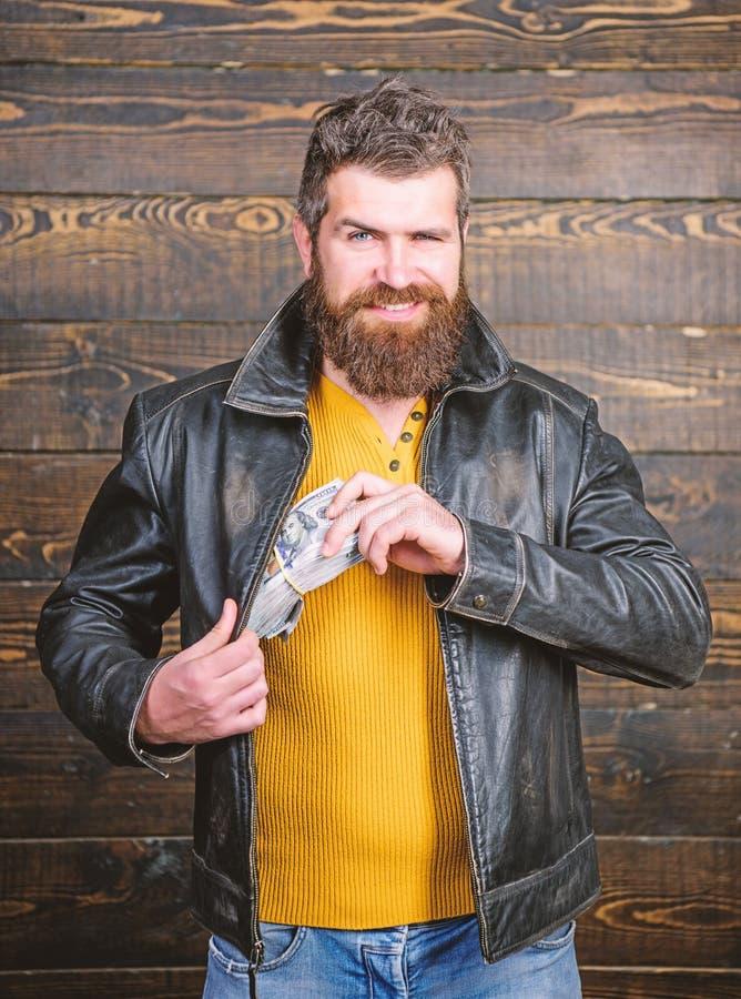 Hippie barbu brutal d'homme utiliser la veste en cuir et tenir l'argent d'argent liquide Affaires de Mafia Bénéfice illégal et ar photos stock