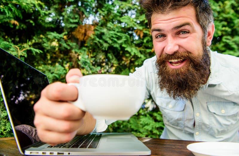 hippie barbu brutal ? la pause-caf? Homme heureux travaillant sur l'ordinateur portatif Perfectionnez l'affaire Employ? de bureau images stock