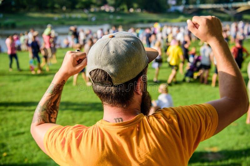Hippie barbu d'homme devant la foule Concert d'air ouvert Billet de livre maintenant Vente t?t d'oiseau Festival de musique diver photographie stock libre de droits