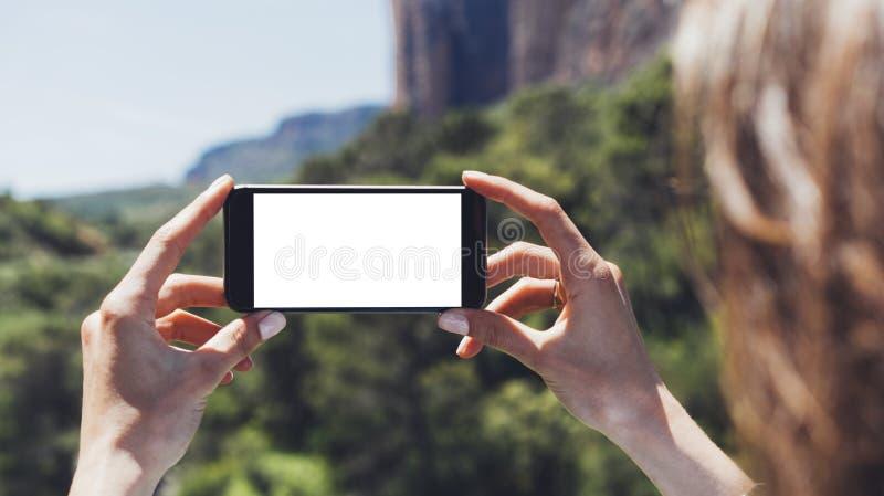 Hippie Bloggermädchen hält Handy in den weiblichen Händen, machen Fotophoto von Naturlandschaft an einem sonnigen Sommertag stockfoto