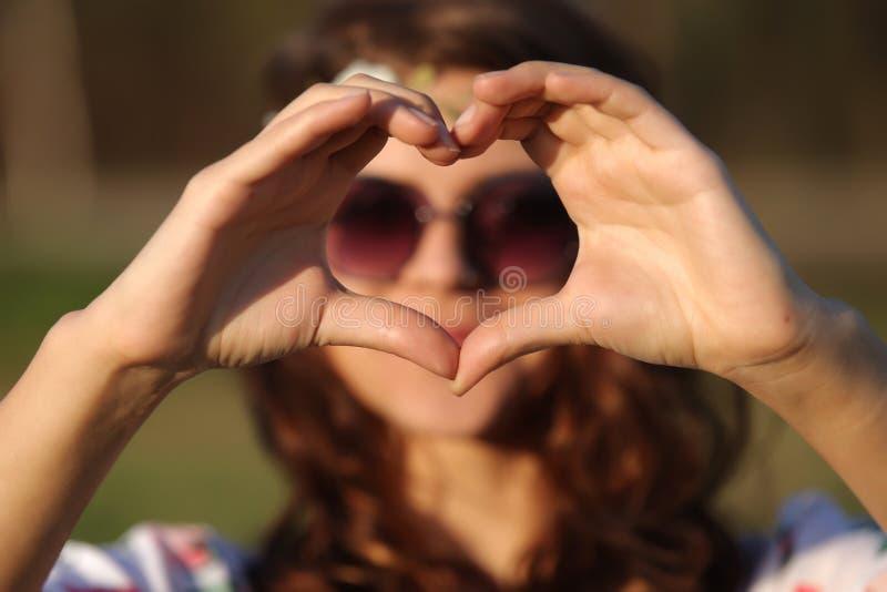 Hippie bonita da mulher que faz o coração e as mostras das mãos ele fora fotos de stock royalty free