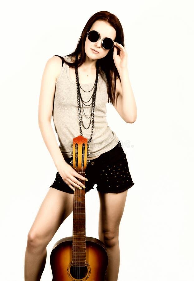 Hippie bonita nova que joga a guitarra no fundo claro foto de stock royalty free