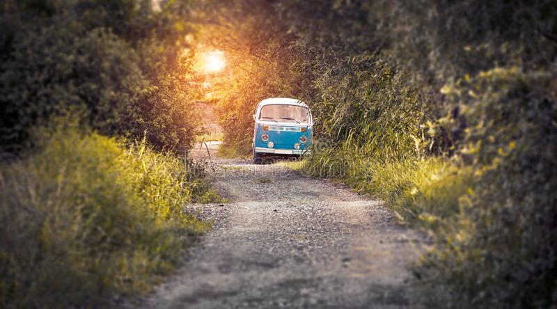 Hippie bus on the road in sunset stock images