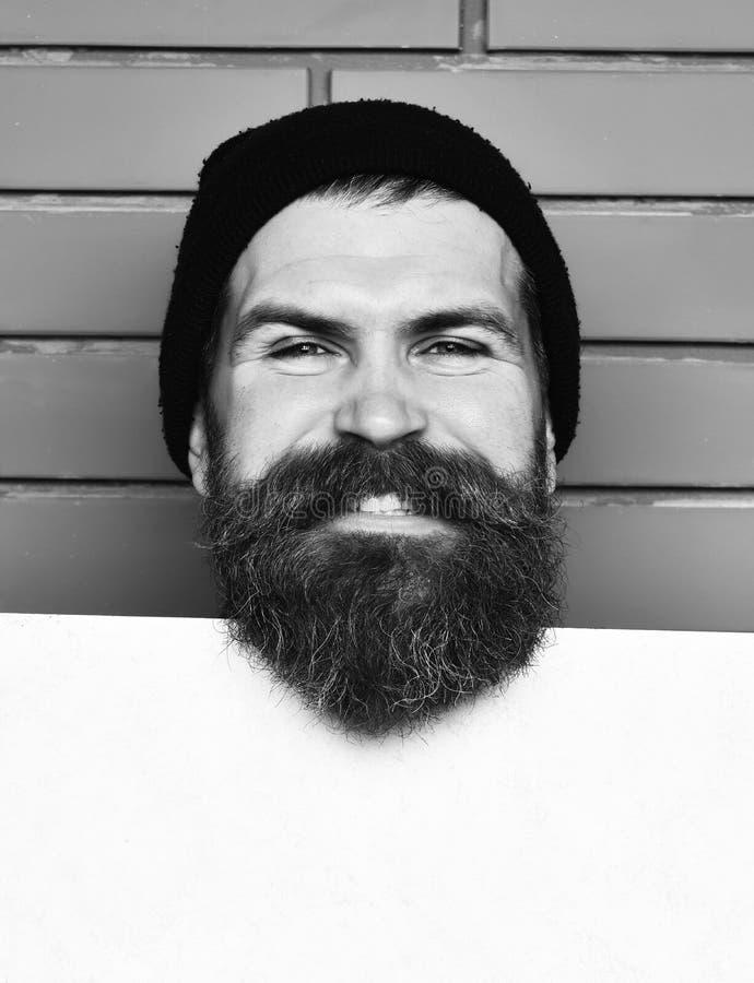 Hippie caucasien brutal barbu avec la feuille de livre blanc photographie stock libre de droits