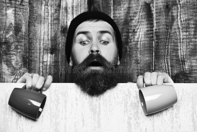Hippie caucasien brutal barbu avec la feuille et les tasses de papier image libre de droits
