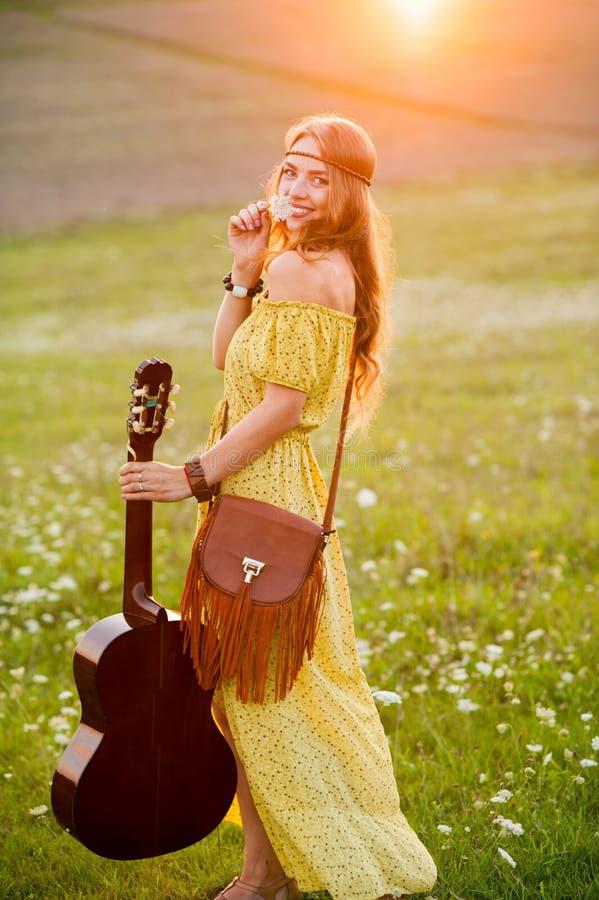 hippie chica con guitarra bailando en el campo al atardecer imagenes de archivo