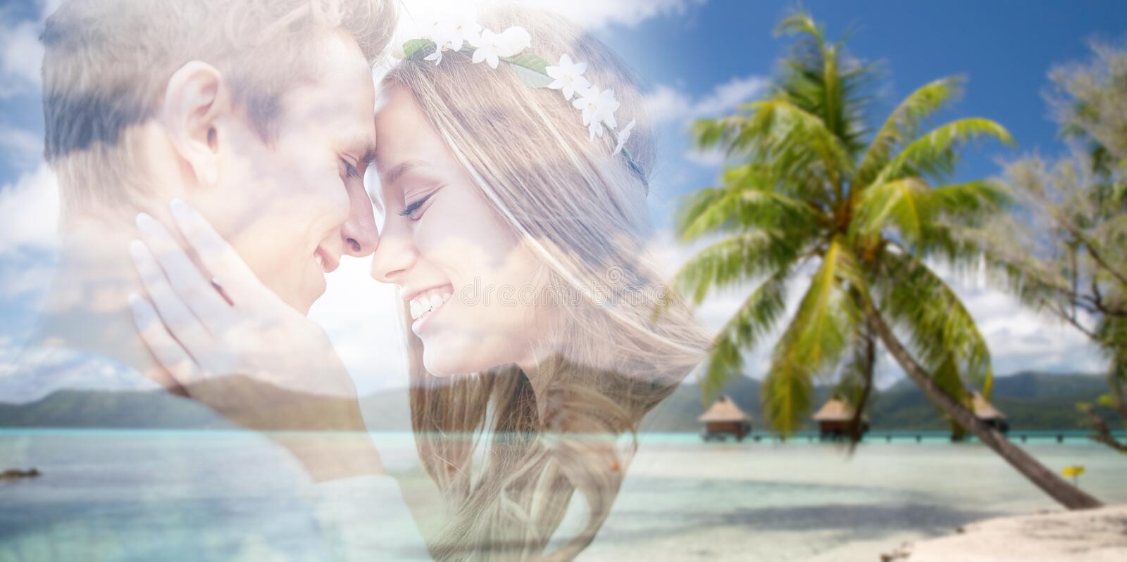 Hippie couple fading over exotic beach background royalty free stock images