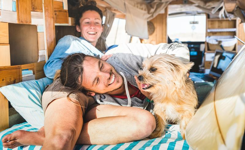 Hippie couple with funny dog traveling together on vintage minivan transport - Life inspiration concept with indie people on mini stock photo