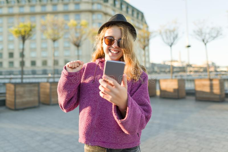Hippie de l'adolescence de fille en chapeau et verres avec le téléphone portable image libre de droits