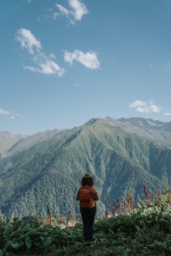 Hippie de voyageuse de femme avec le sac à dos regardant en avant les montagnes étonnantes et la vue de vallée photos libres de droits