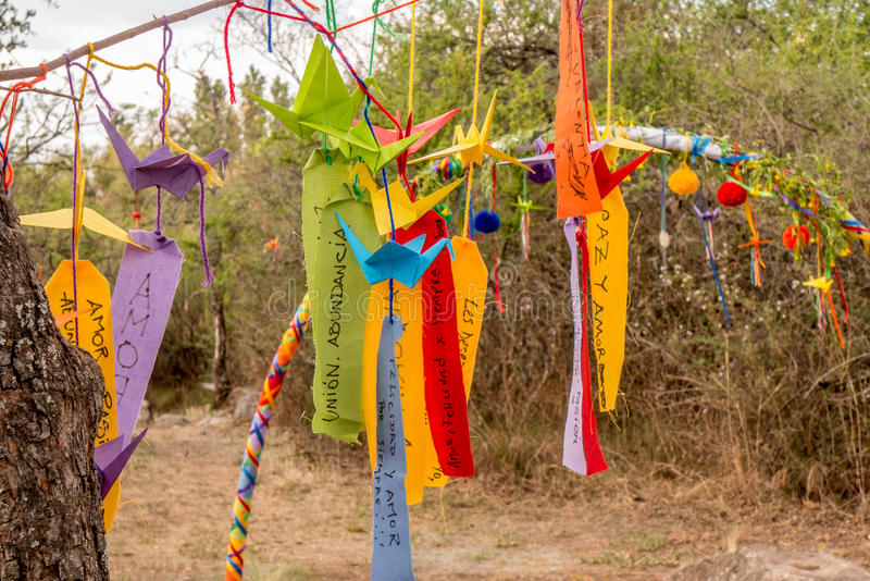 A hippie decoration. A celebration in the bushes, with hanging wishes and words in spanish love, peace, abundance, union, etc royalty free stock photography
