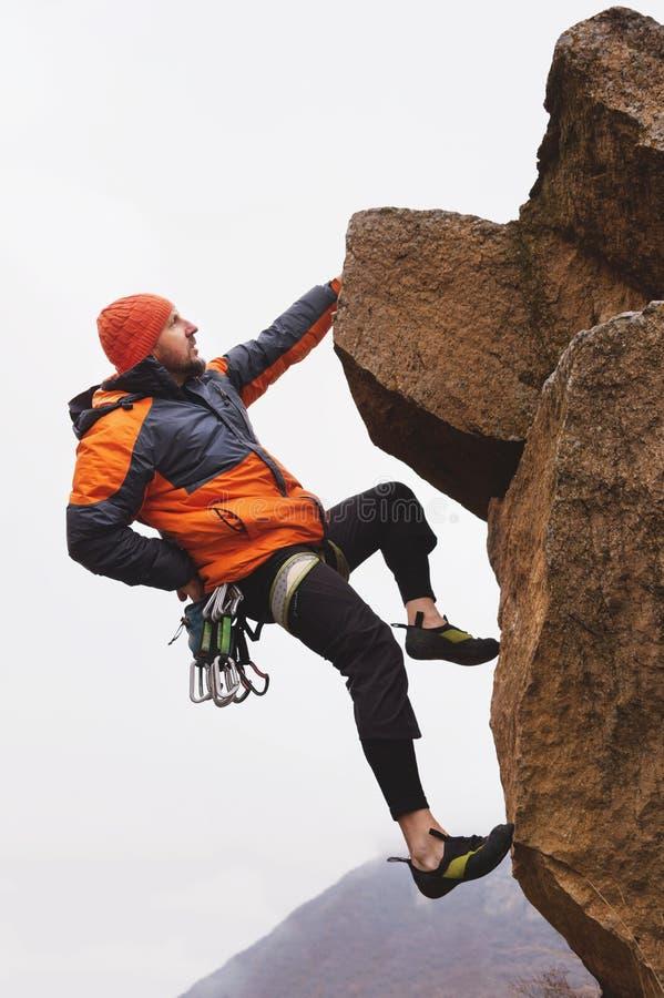 Hippie - einerseits hängender Bergsteiger an einem Felsen gegen den Hintergrund der kaukasischen Berge im Spätherbst lizenzfreie stockfotos