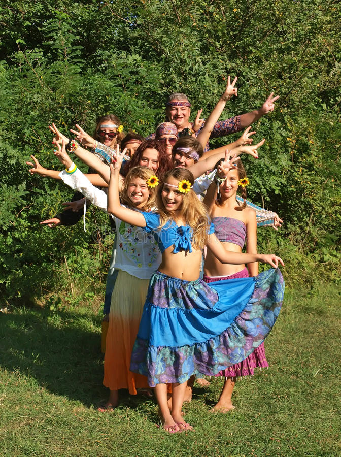 Hippie family. Portrait of a large smiling-happy family (best friends) of hippies showing sign of peace. Vertical color photo