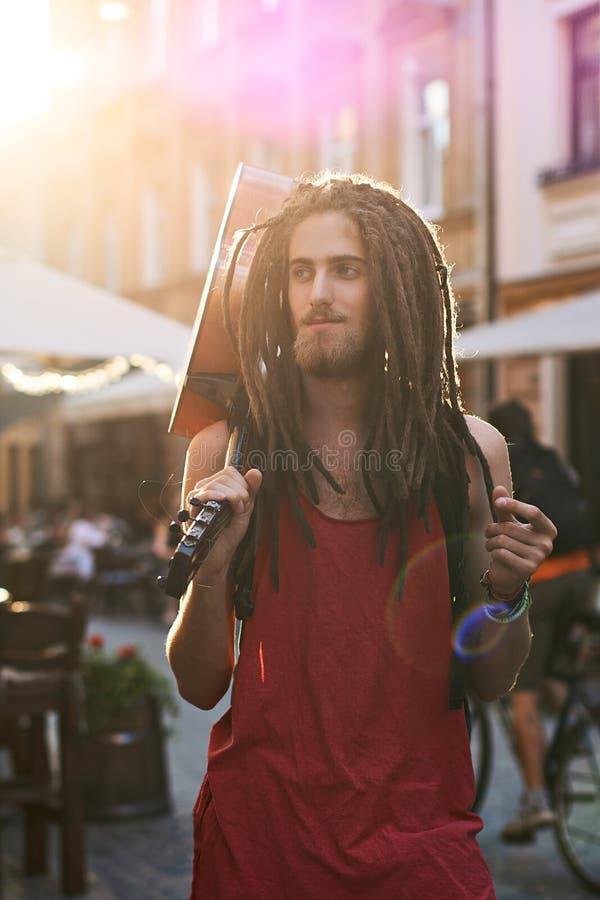 Hippie farpada considerável nova do homem com os dreadlocks que agarram os dedos em uma rua velha da cidade completamente da luz  fotos de stock royalty free