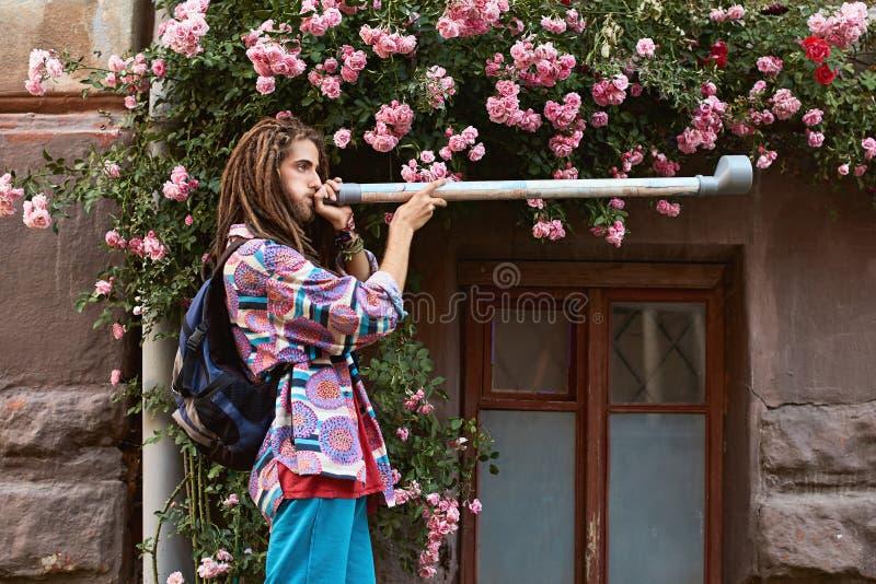 Hippie farpada considerável nova do homem com os dreadlocks que jogam a tubulação do fundo cor-de-rosa das rosas imagens de stock