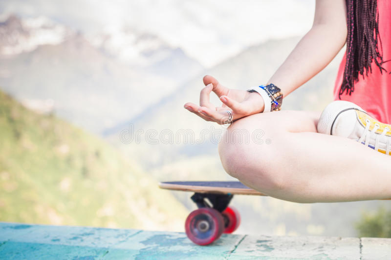 Hippie fashion girl doing yoga, relaxing on skateboard at mountain. Closeup image of hippie fashion girl doing yoga, relaxing and sitting on skateboard at stock image