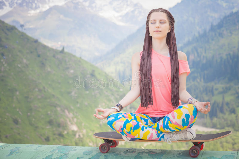 Hippie fashion girl doing yoga, relaxing on skateboard at mountain. Hippie fashion girl doing yoga, relaxing and sitting on skateboard at mountain. Concept of royalty free stock photo