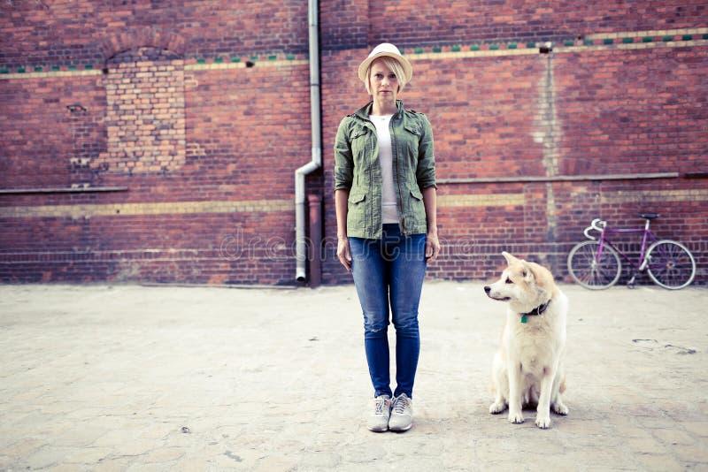 Hippie-Frau mit Hund und Weinleserennrad in der Stadt stockfotografie