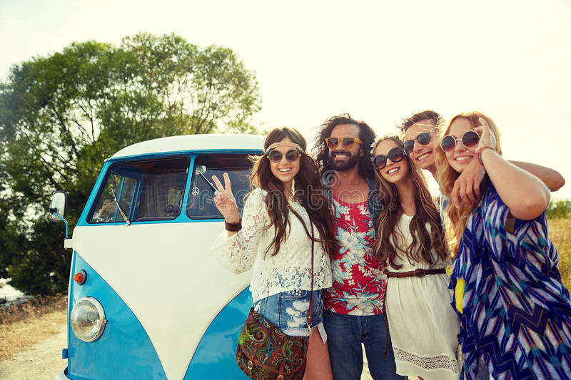 Hippie friends over minivan car showing peace sign. Summer holidays, road trip, vacation, travel and people concept - smiling young hippie friends over minivan stock image