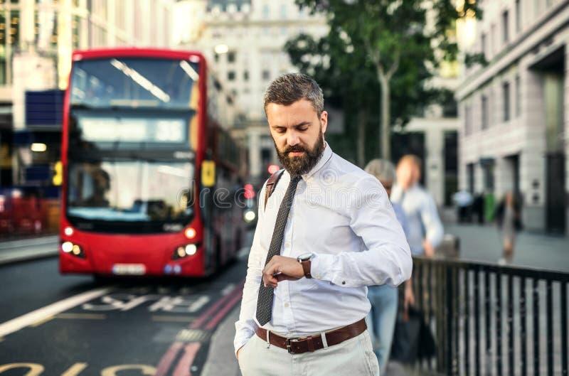 Hippie-Geschäftsmann, der auf den Bus in London, die Zeit überprüfend wartet stockbild