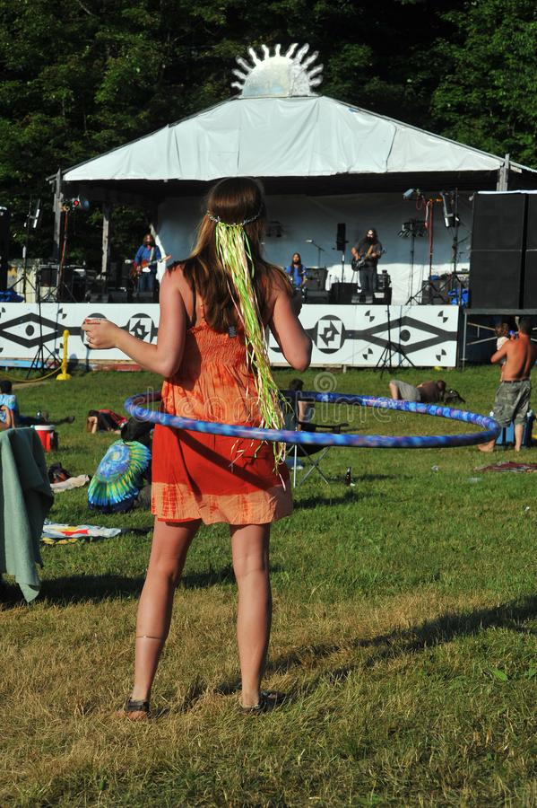 Hippie girl doing hula hoop. Hippie girl in orange colored dress doing the hula hoop at an outdoor concert held in a green grassy field stock image