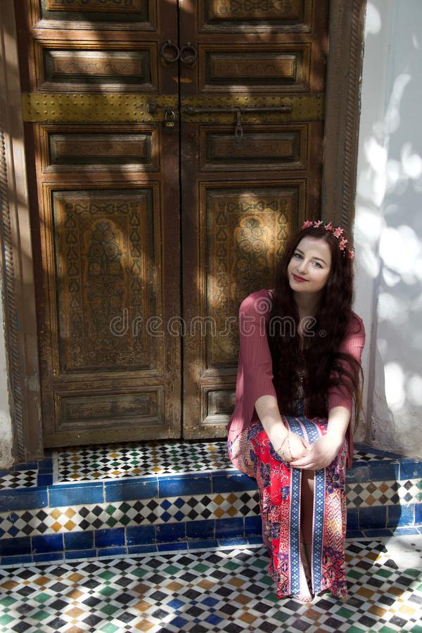 Hippie girl in a doorway. A hippie girl wearing pink clothes and hair flowers sits in a Moroccan doorway royalty free stock image