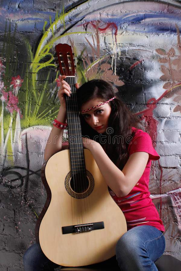 Hippie girl with guitar. In front of a graffiti brick wall, looking straight stock photography