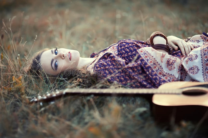 Hippie girl with guitar. Beautiful hippie girl with guitar lying on the grass royalty free stock images