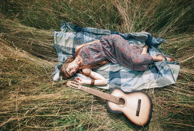 Hippie girl with guitar lying on the mowed grass stock images