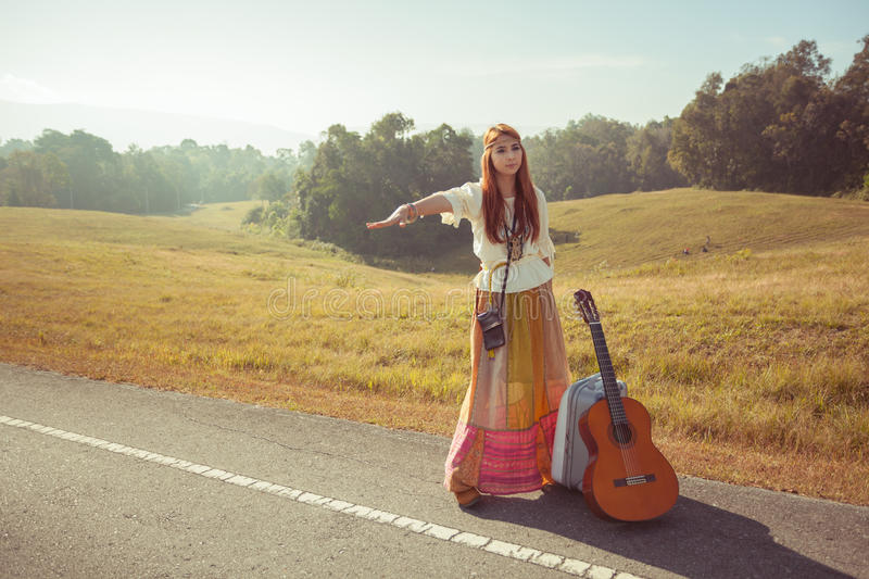 Hippie girl hitchhiking. Hippie girl with guitar hitchhiking on countryside road royalty free stock photography