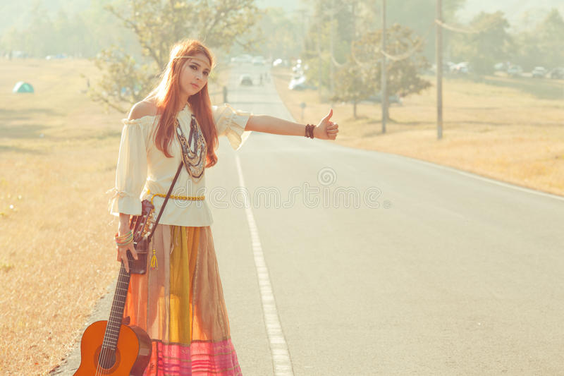 Hippie girl hitchhiking. Hippie girl with guitar hitchhiking on countryside road royalty free stock images