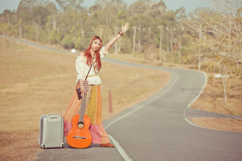 Hippie girl hitchhiking. Hippie girl with guitar hitchhiking on countryside road royalty free stock photo