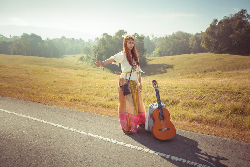 Hippie girl hitchhiking. Hippie girl with guitar hitchhiking on countryside road stock photo