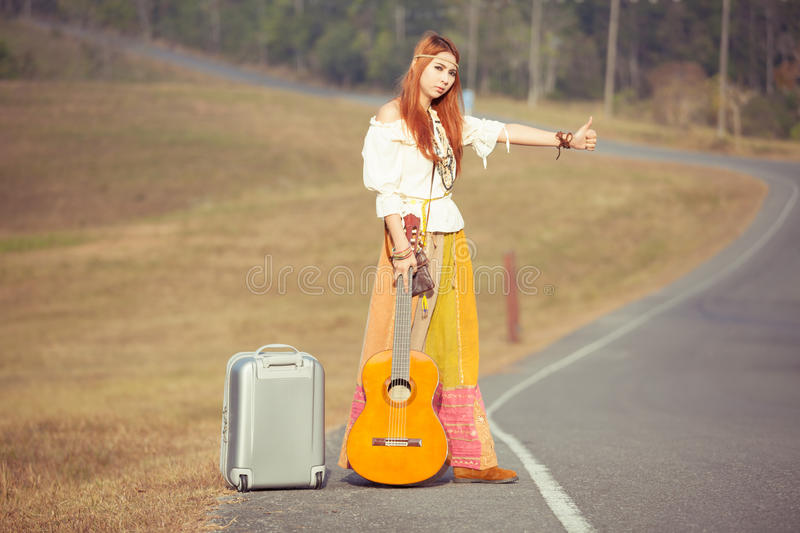 Hippie girl hitchhiking. Hippie girl with guitar hitchhiking on countryside road stock photos