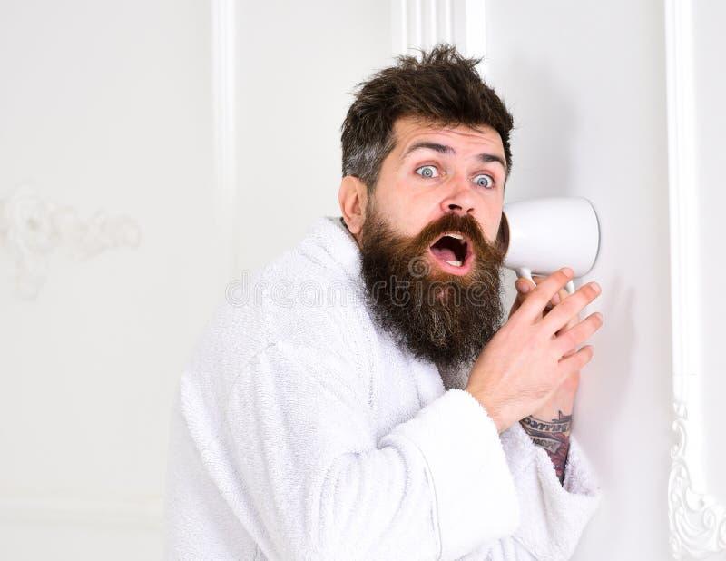 Hippie im Bademantel auf entsetztem Gesicht hören geheim Gespräch Geheimnis und Spionskonzept Mann mit Bart und dem Schnurrbart lizenzfreies stockfoto
