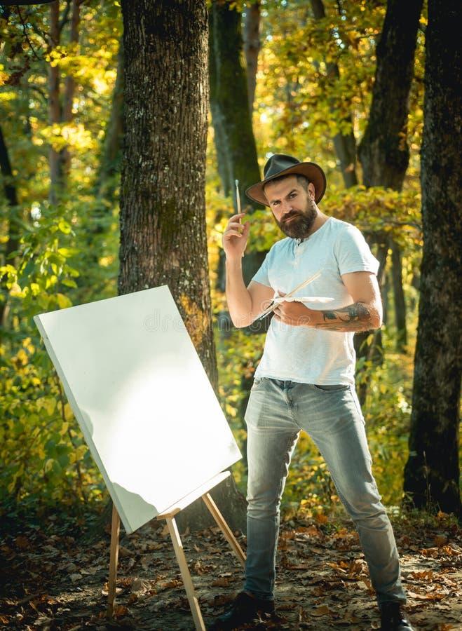 Hippie-Künstler in einem Hut, der im Wald Kunst schafft Wei?e Schablone mit rotem Punkt des Lackes auf schwarzem Hintergrund Male lizenzfreie stockfotografie