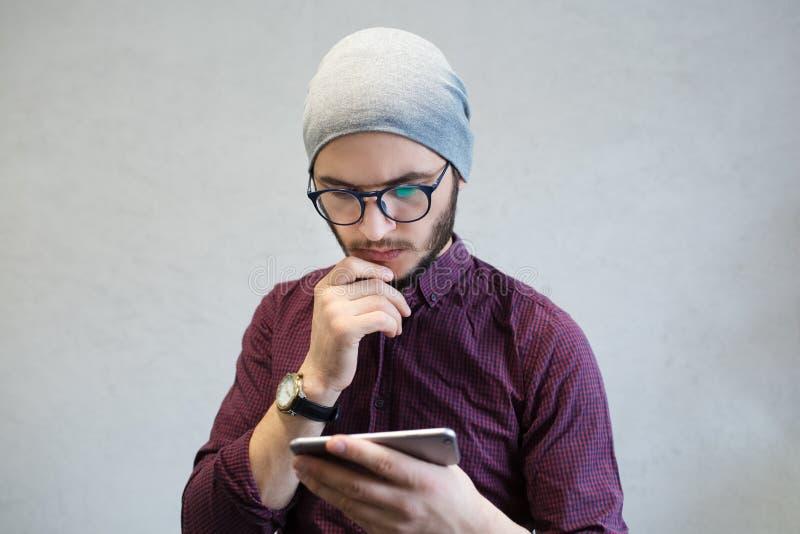 Hippie-Kerl, der smarphone auf Hintergrund von Weiß verwendet lizenzfreie stockbilder