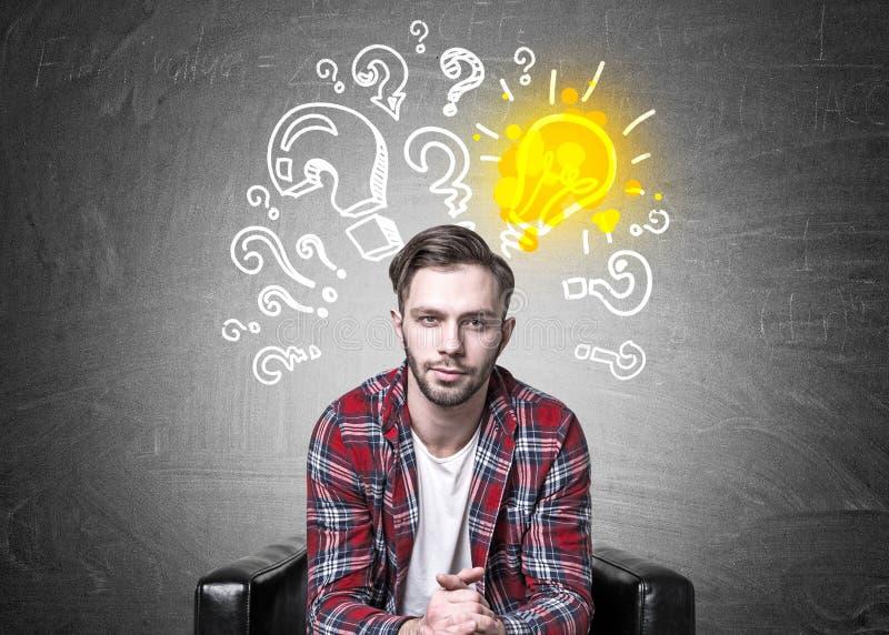 Hippie-Kerl in einem Lehnsessel, in den Fragen und in der Idee lizenzfreie stockfotos