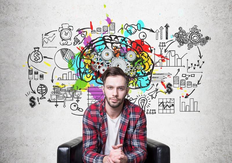 Hippie-Kerl in einem Lehnsessel und in den Gehirnzähnen stockfoto