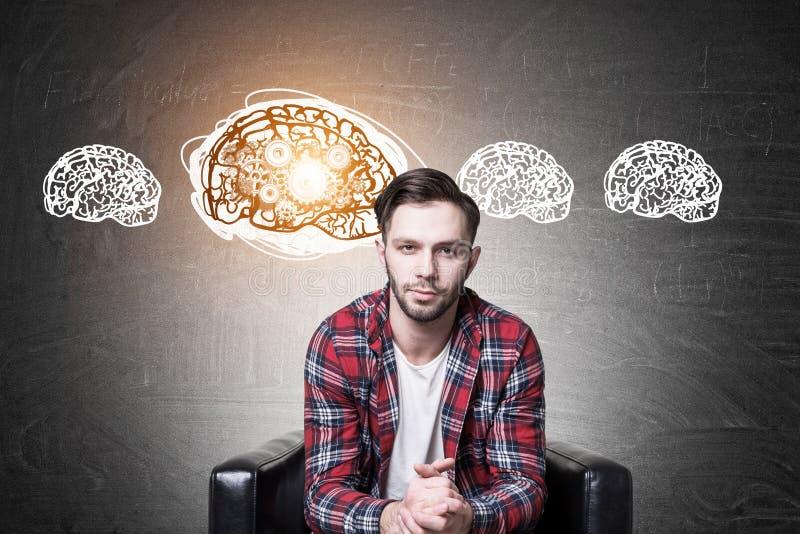 Hippie-Kerl in einem Lehnsessel und in vier Gehirnzähnen lizenzfreie stockfotos