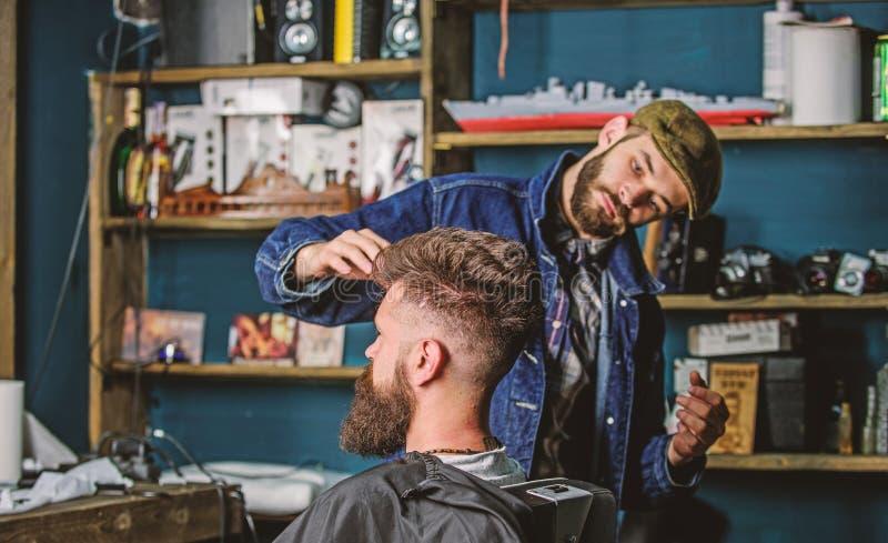 Hippie-Kunde mit neuem Haarschnitt oder Frisur Friseur, der Haar des bärtigen Kunden mit Wachs durch Hände anredet friseursalon lizenzfreie stockfotos