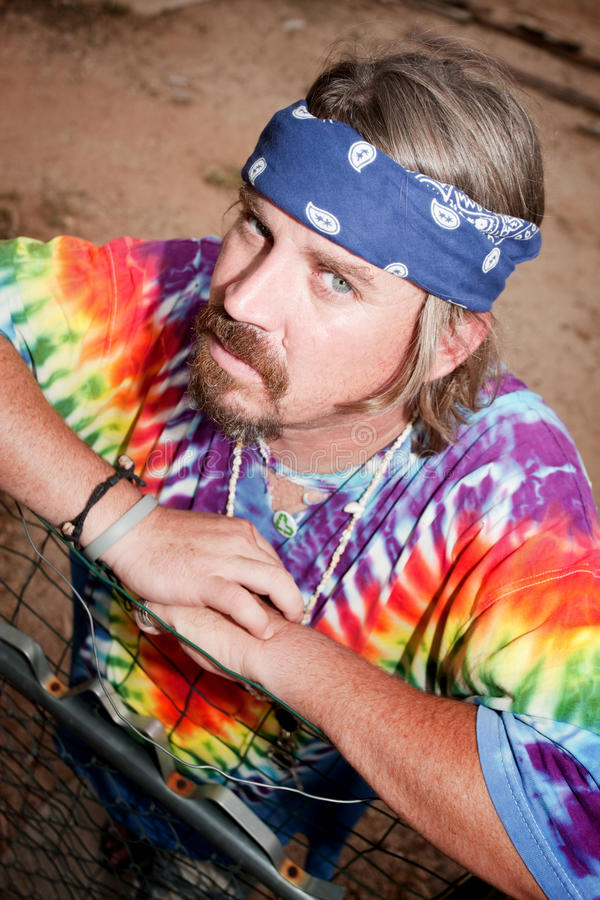 Hippie leaning on a gate stock photography