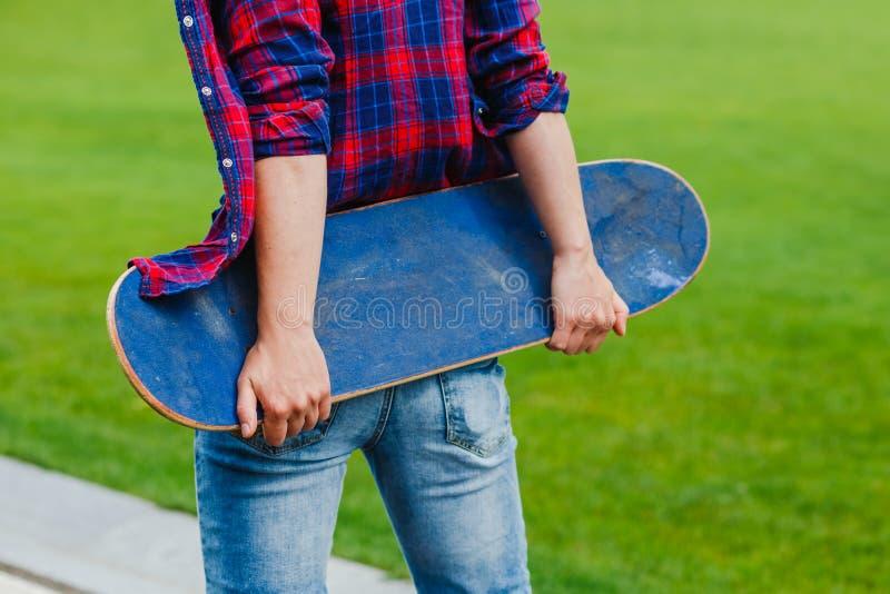 Hippie-Mädchen auf der Landstraße, die ein Skateboard in den Händen hält stockfotografie