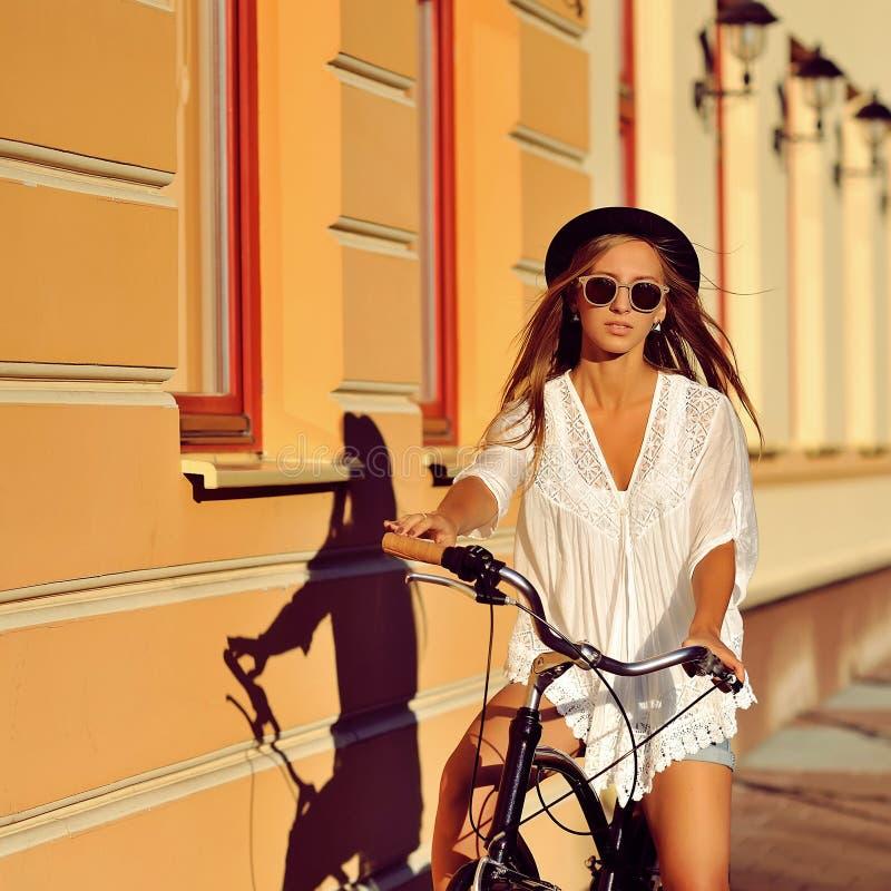 Hippie-Mädchen auf einem Weinlesefahrrad - Modeporträt im Freien stockbild