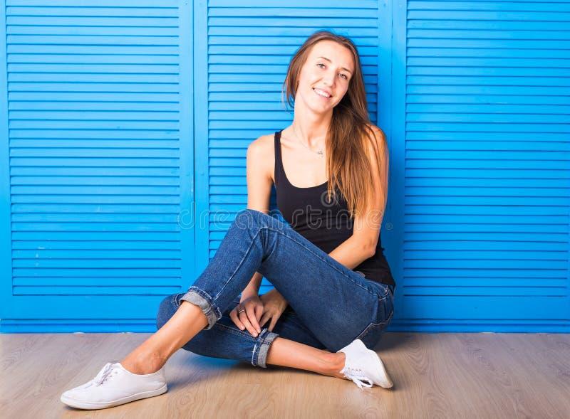Hippie-Mädchen, das auf dem Boden gegen blauen Hintergrund sitzt lizenzfreie stockbilder